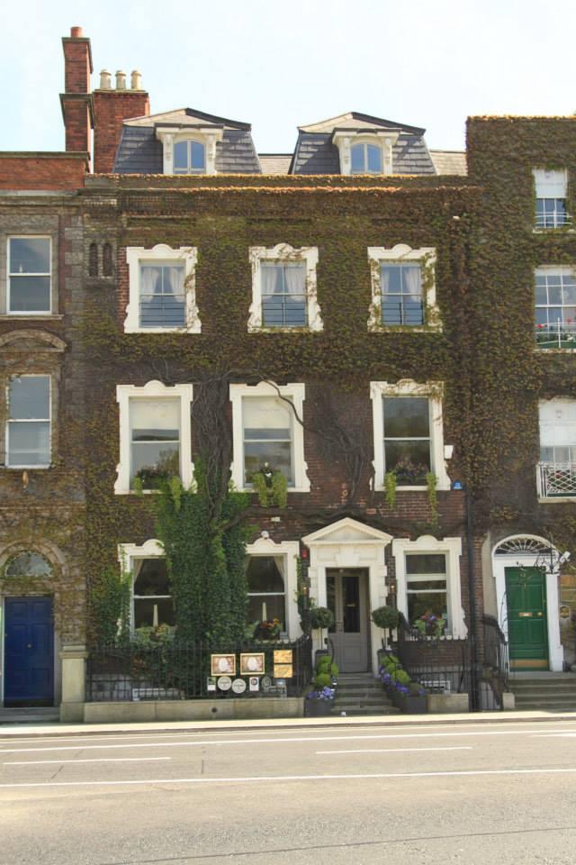 Façade d'un hôtel particulier irlandais typique. On distingue la petite porte géorgienne typique ainsi que la jolie couverture de lierre sur l'ensemble de la bâtisse.